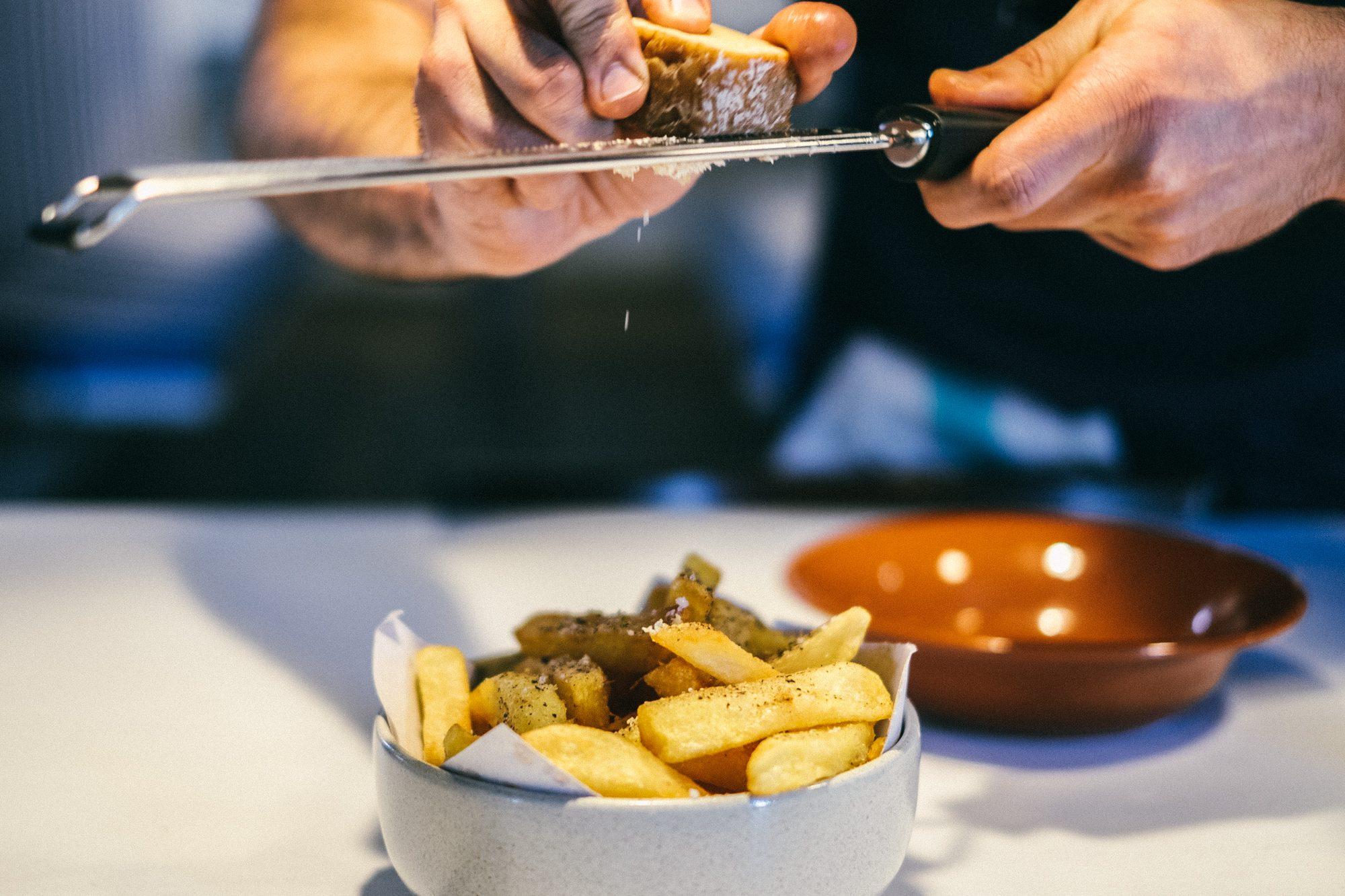 Aquele momento épico em que Bruno rala o toucinho curado sobre as batatas fritas da casa. (foto: © Tiago Pais / Observador)