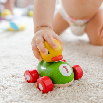 Freepik home visit living room floor baby-playing-with-wooden-car_53876-70985.jpg