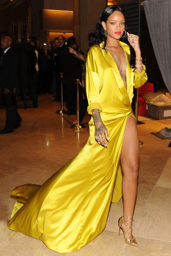 Rihanna wears a yellow silky gown with high split to the pre-grammy's party on January 26, 2014.