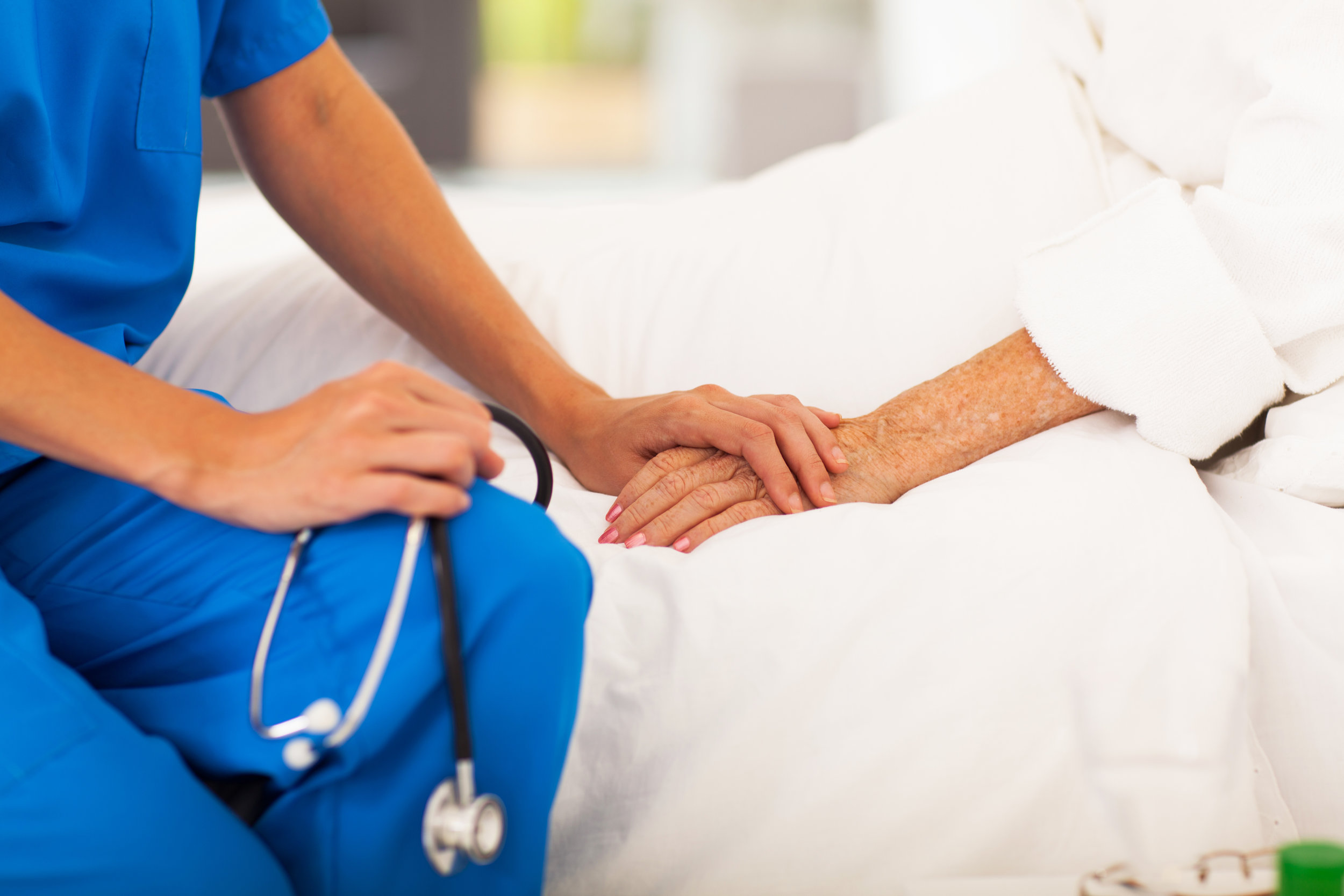 Nurse holding the hand of a patient in a skilled nursing facility