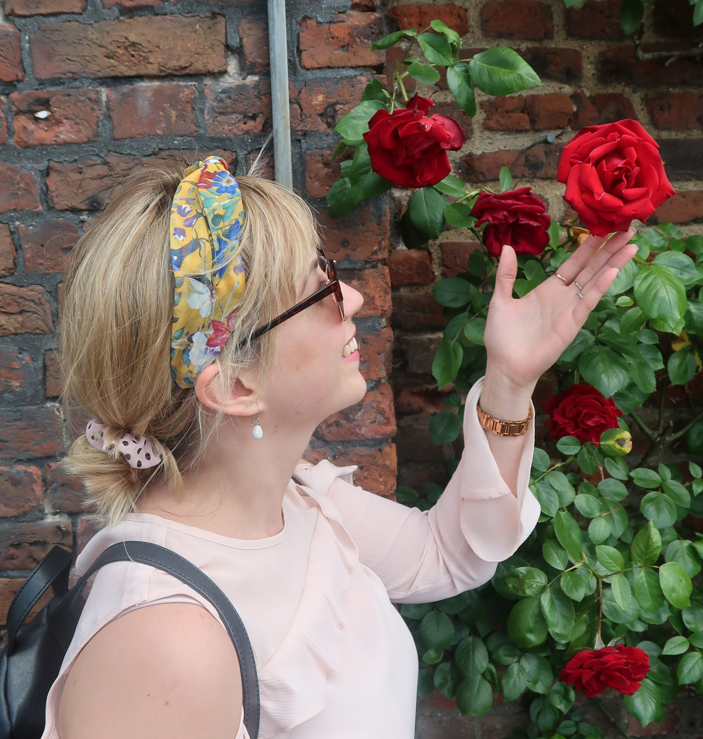 Literally stopping to smell the roses.  Hampton Court, England.