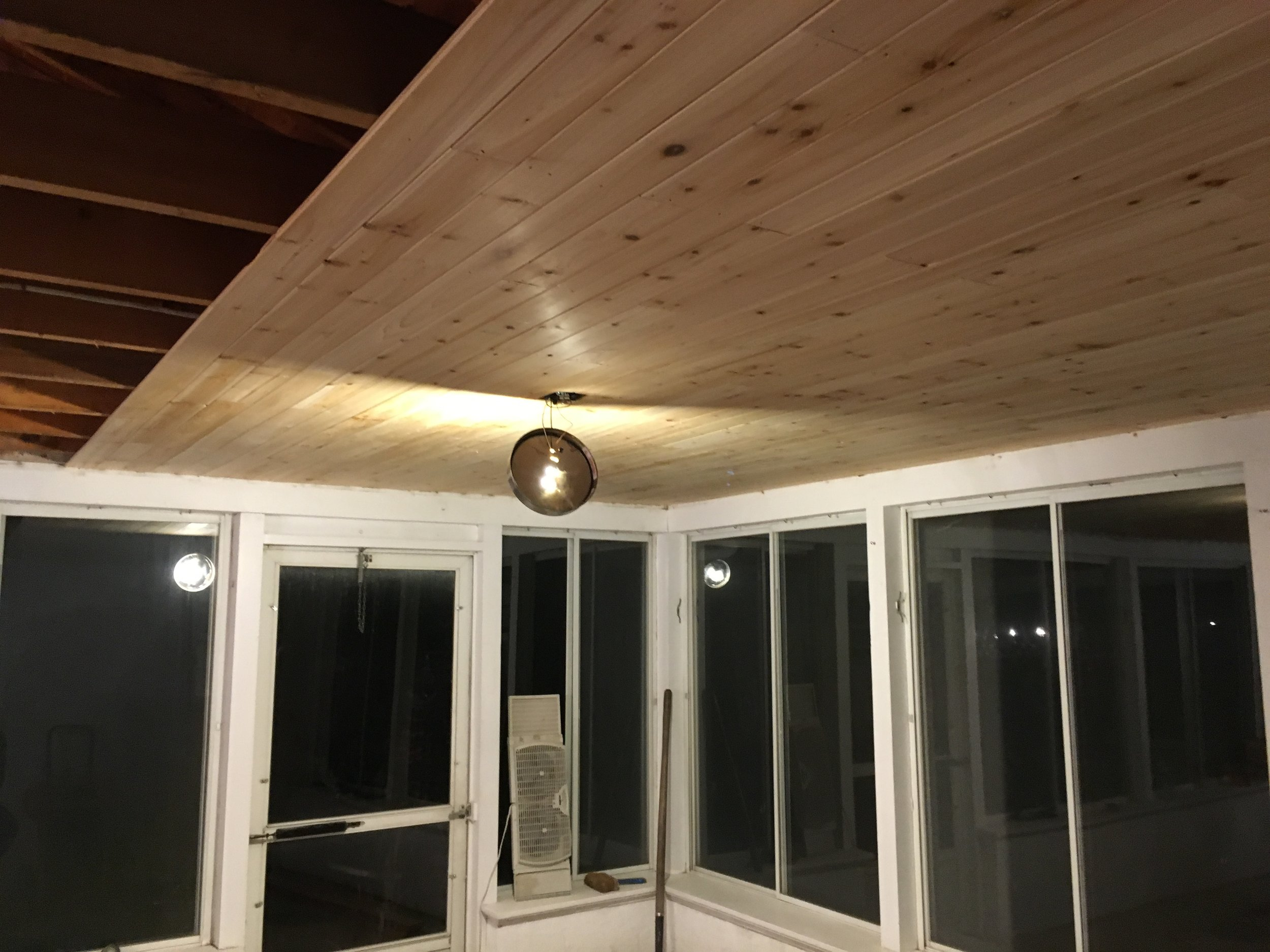 When I saw the plan that he had for the ceiling, I felt better about the SURPRISE ceiling removal.  He used cedar to create a new ceiling in the room. This is what it looked like in progress, and before we stained the raw wood.