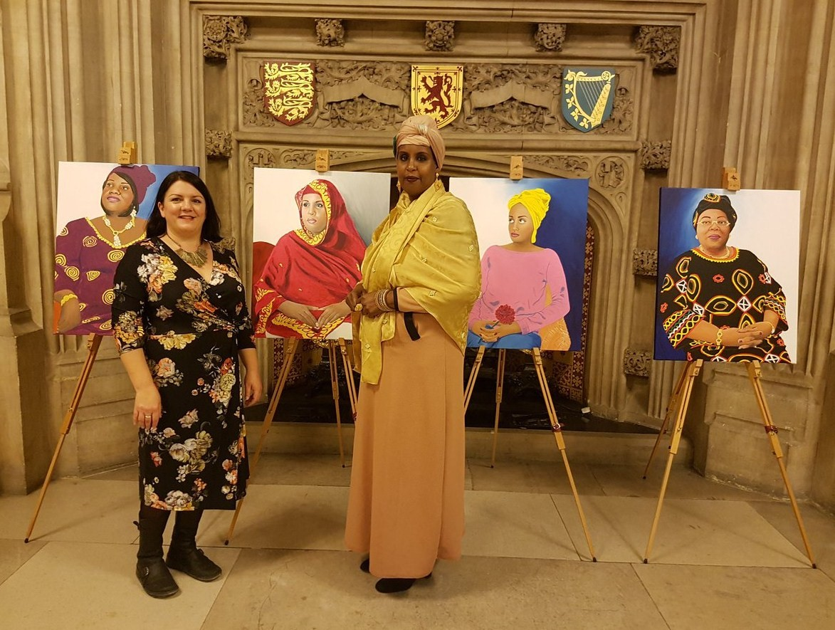 Emma and Hibo Wardere with her portraits of FGM survivors at Houses of Parliament exhibition