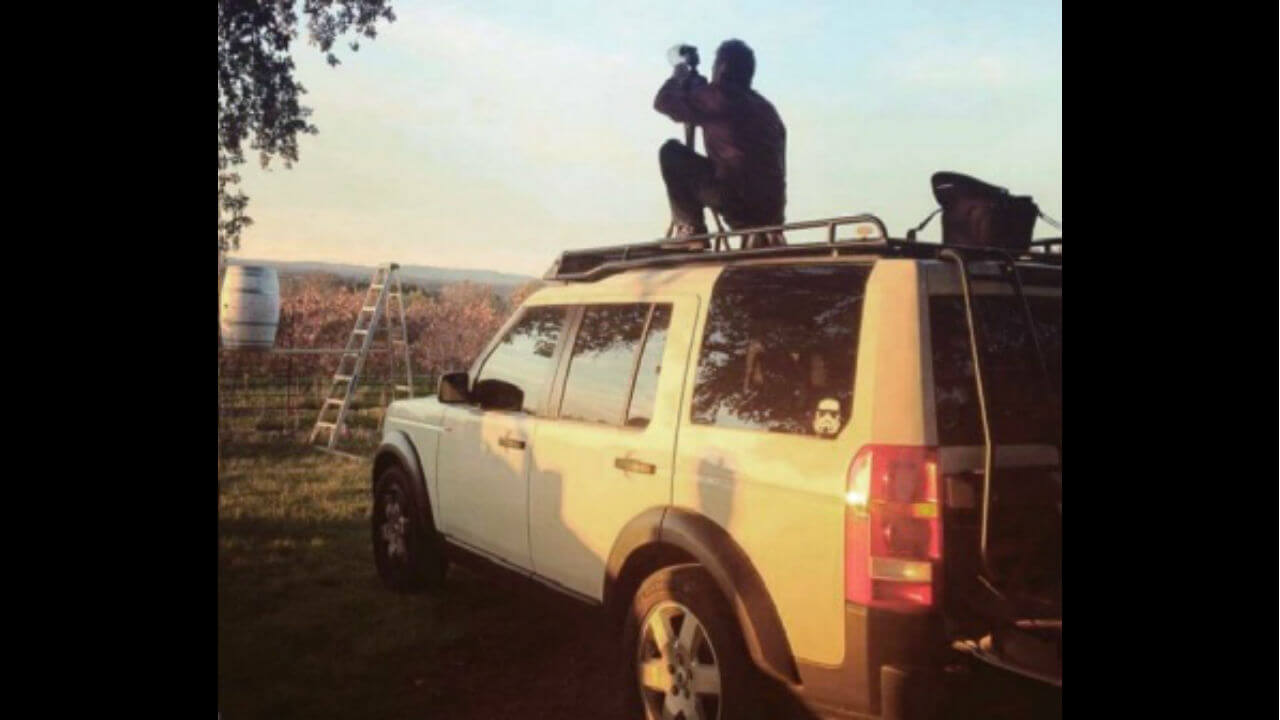 Land-Rover-LR4-white-off-road--Voyager-low-profile-roof-rack-photographer-on-roof-Voyager-Offroad.jpg