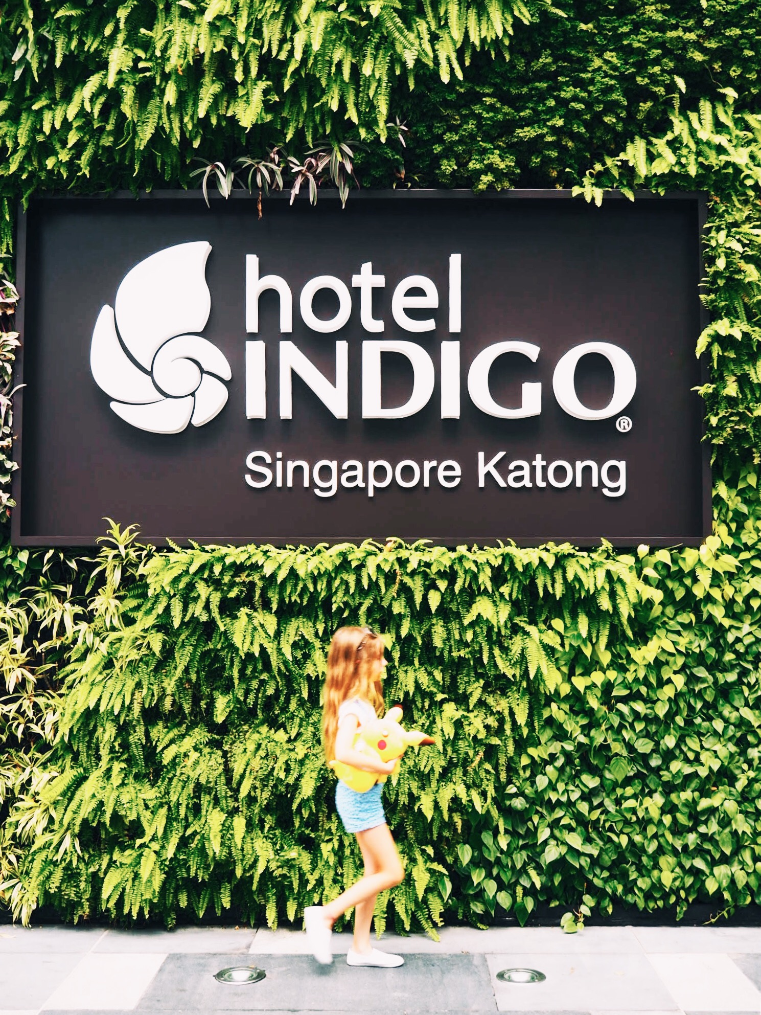 The discreet entrance to the Hotel Indigo Singapore Katong, concealed behind a wall of greenery.