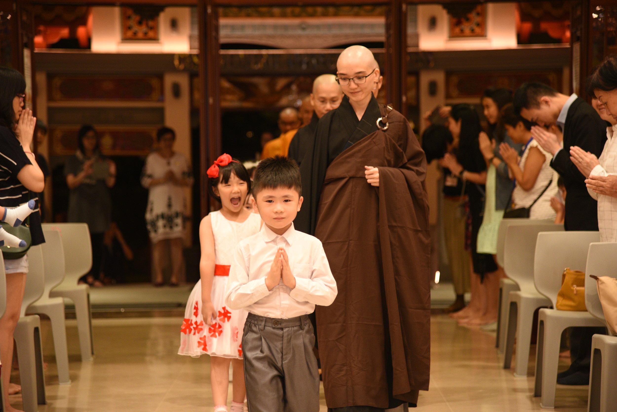 铃声敲响,由僧团法师们牵引着小手缓缓进殿。
