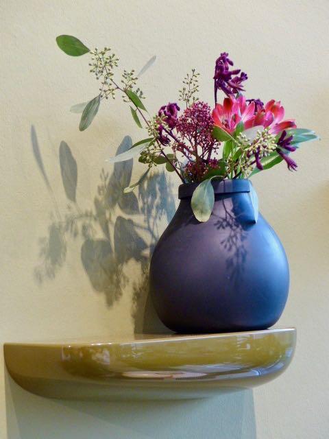 blaue Blumenvase auf goldenem Regal