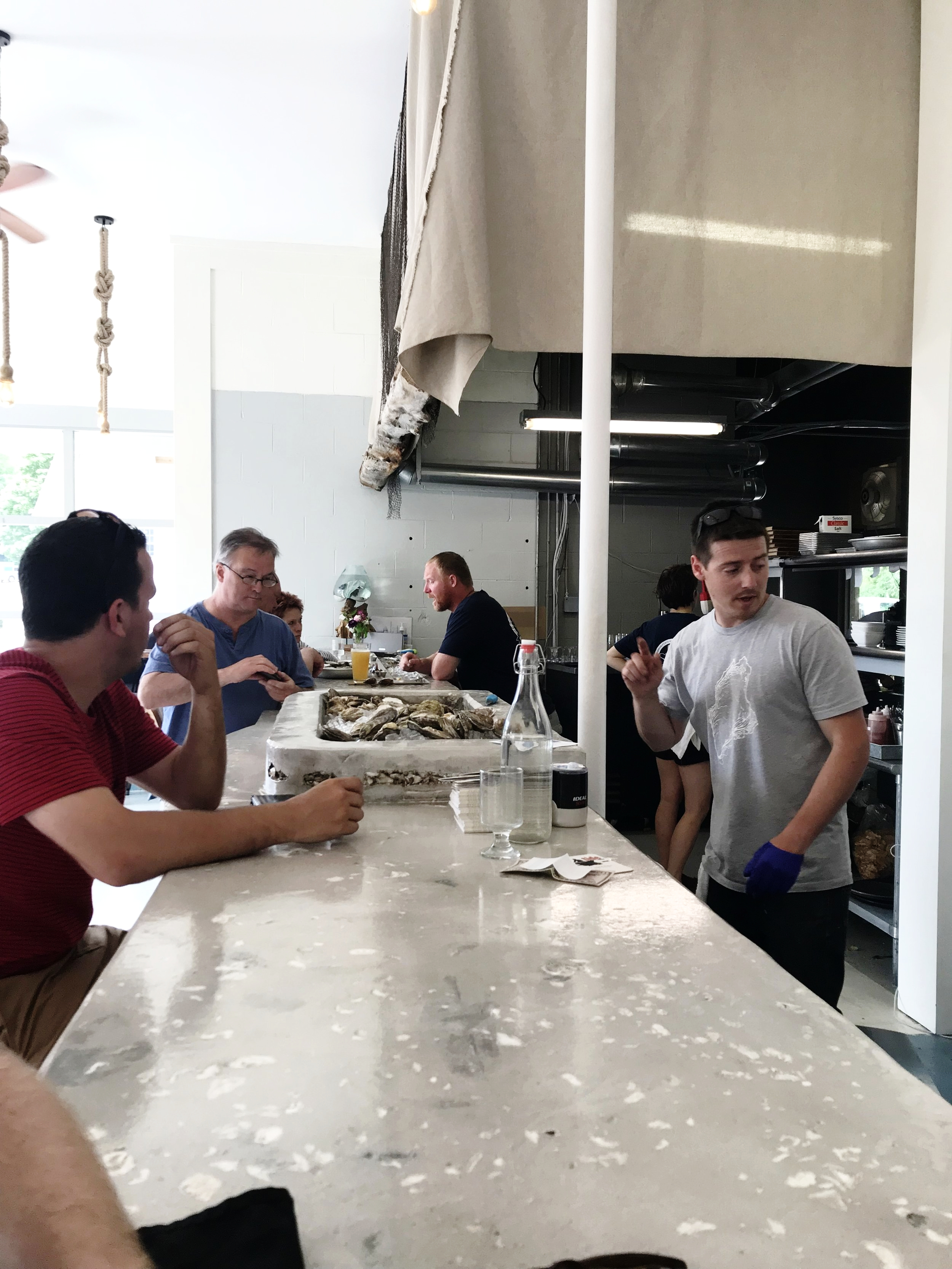 The bar fused with oyster shell, and Brendan pausing for a moment from shucking.