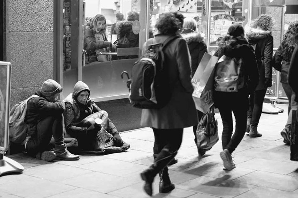 Photo-of-David-Johnston-from-OutsideIn-sitting-on-the-streets-talking-someone-who-is-homeless.jpg