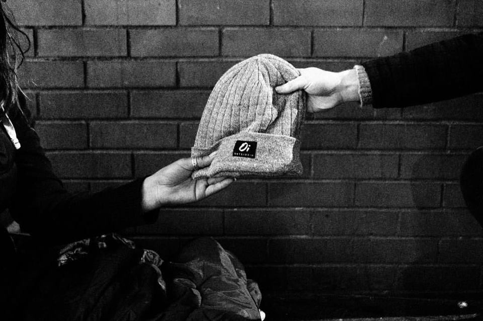 Photo of a hat being given out as  part of the Wear One Share One Model By OutsideIn.jpg
