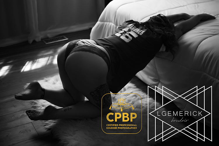 Woman in a Patrick Mahomes jersey stretching forward onto a bed in black and white for boudoir photography by LGEmerick Photography
