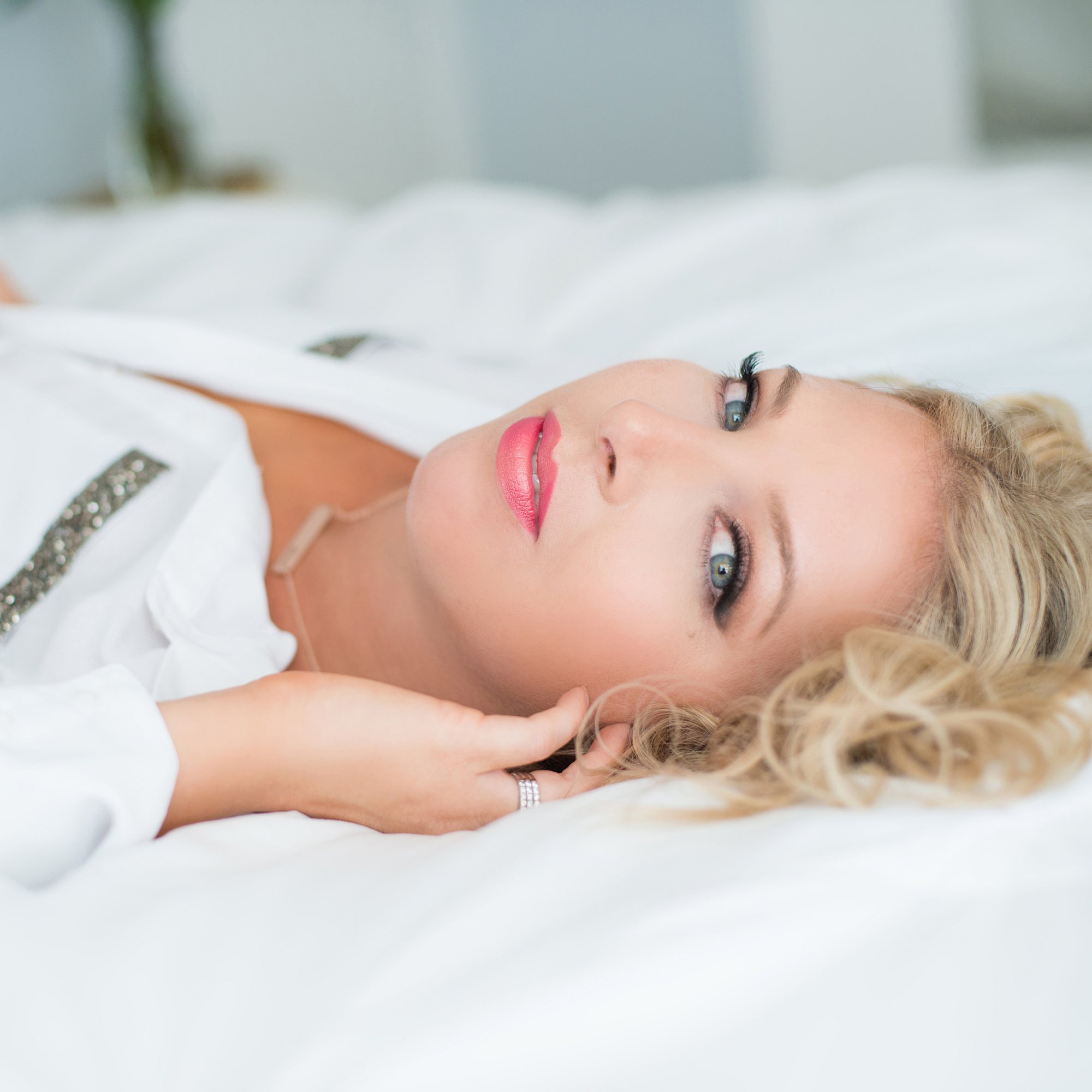 Beautiful blonde woman with piercing blue eyes laying on white bedding at LGEmerick Photography's studio
