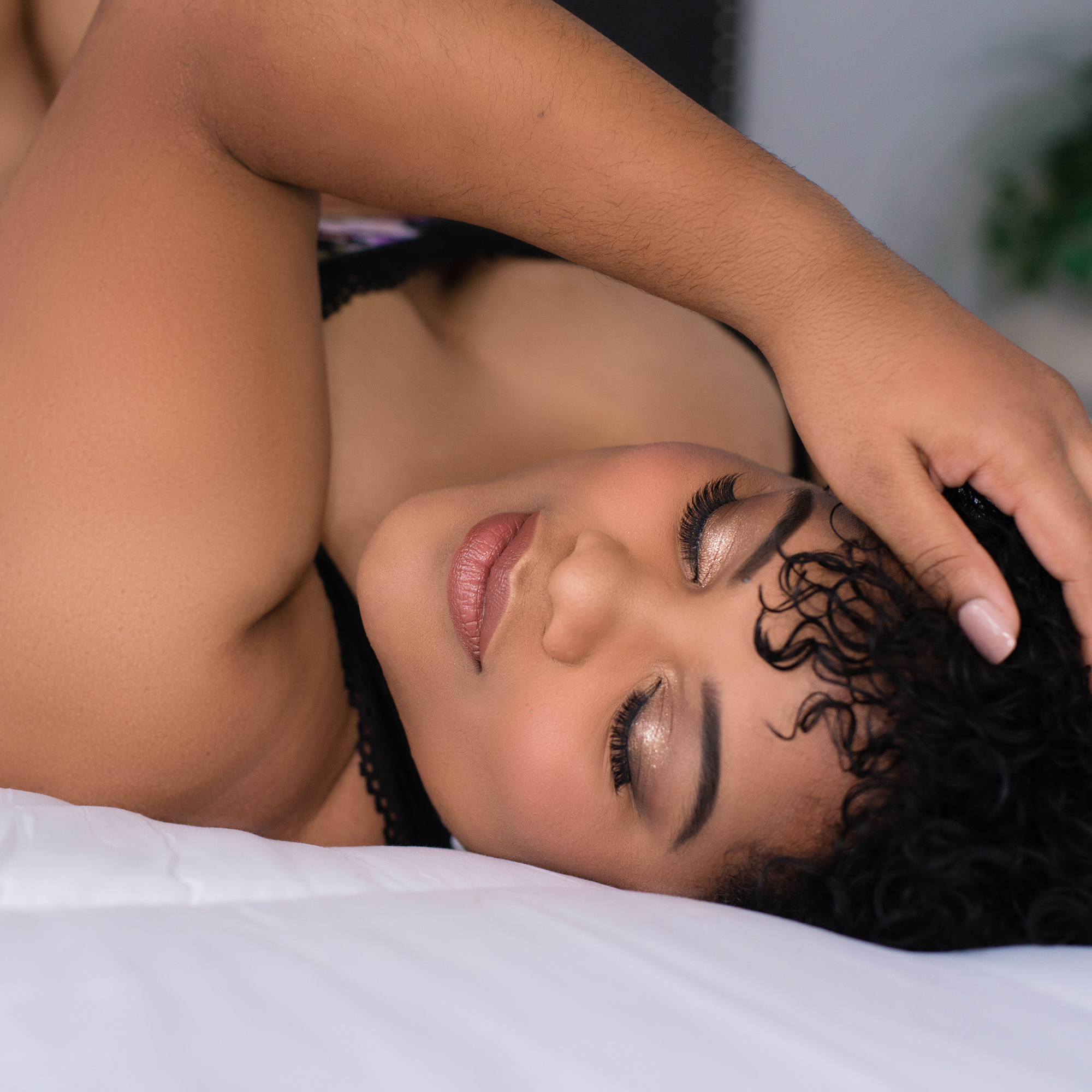 Stunning african american woman with eyes closed on bed smiling in LGEmerick Photohraphy's studio