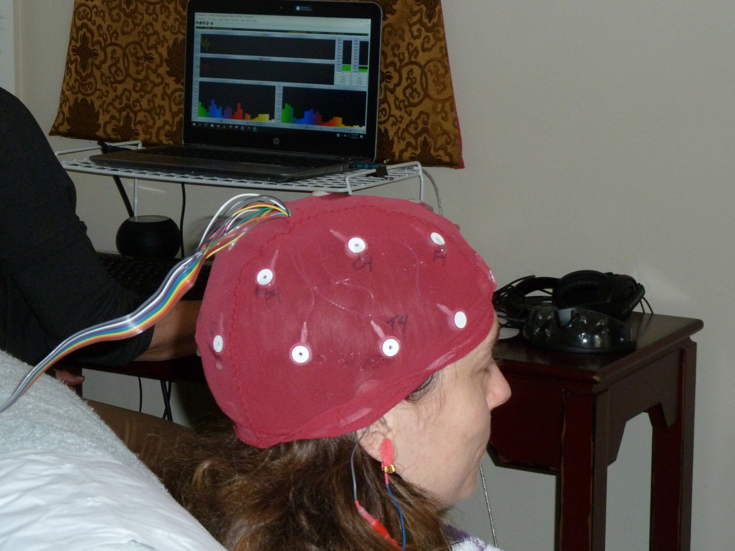 Client wearing cap with electrodes for brain mapping process.