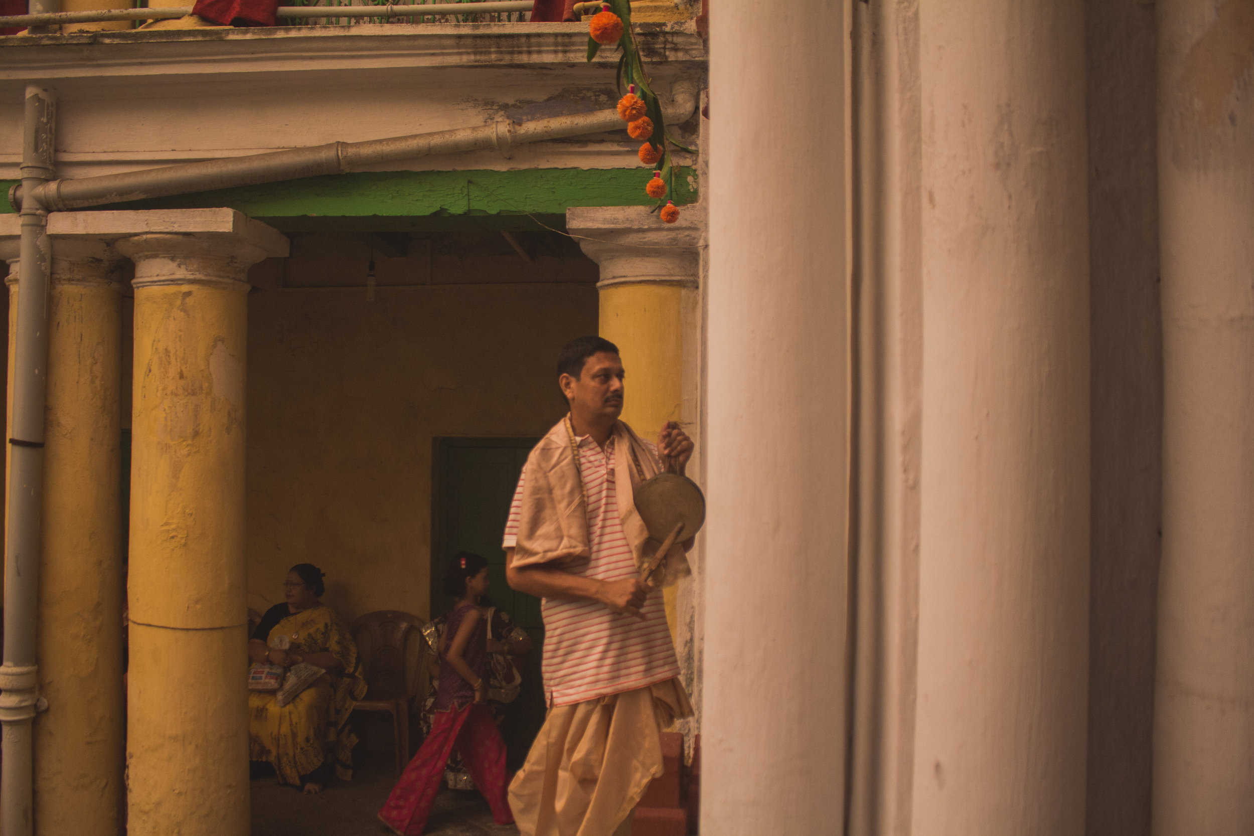 Music is a big part of such ceremonies. Here, a member of the house is seen playing the  kashor , a metal cymbal-like instrument suspended by a rope. The player usually beats the instrument to the rhythm of the  dhak .