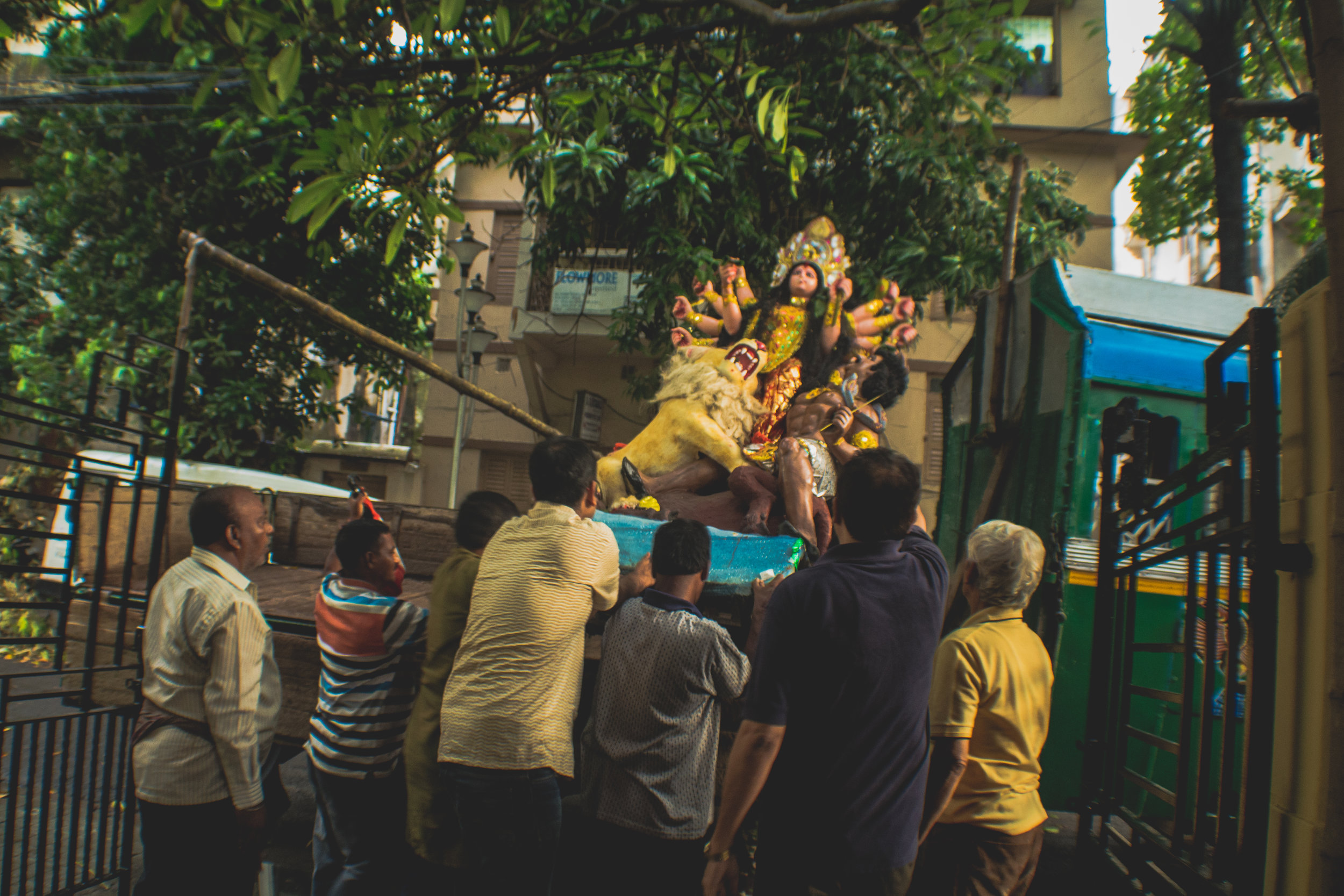 On the day of  Bissarjan , family and friends of the Chatterjee family in South Kolkata heave a home idol onto a truck, to carry her to the Ganges.