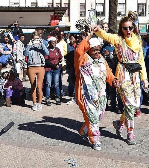 Image: Adele Varcoe and a Onesie recipient at Vrystaat Arts Festival (2017). Photograph courtesy of Vrystaat Arts Festival.