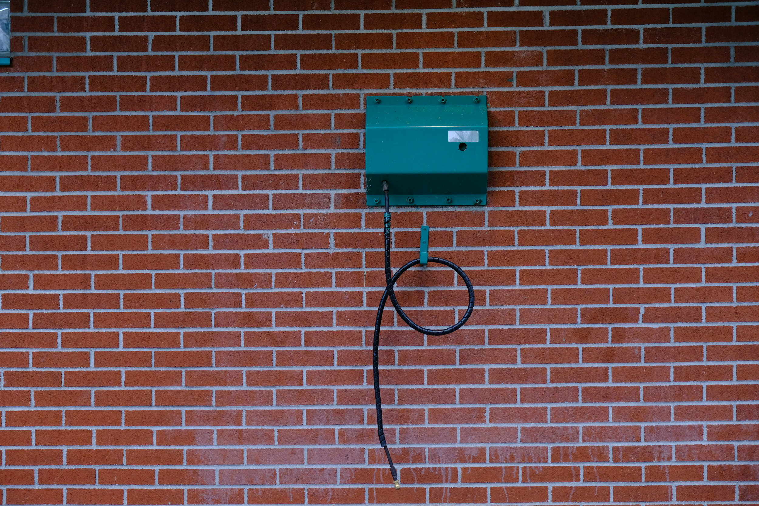 A bike pump attached to the wall of a public restroom in Candiac.