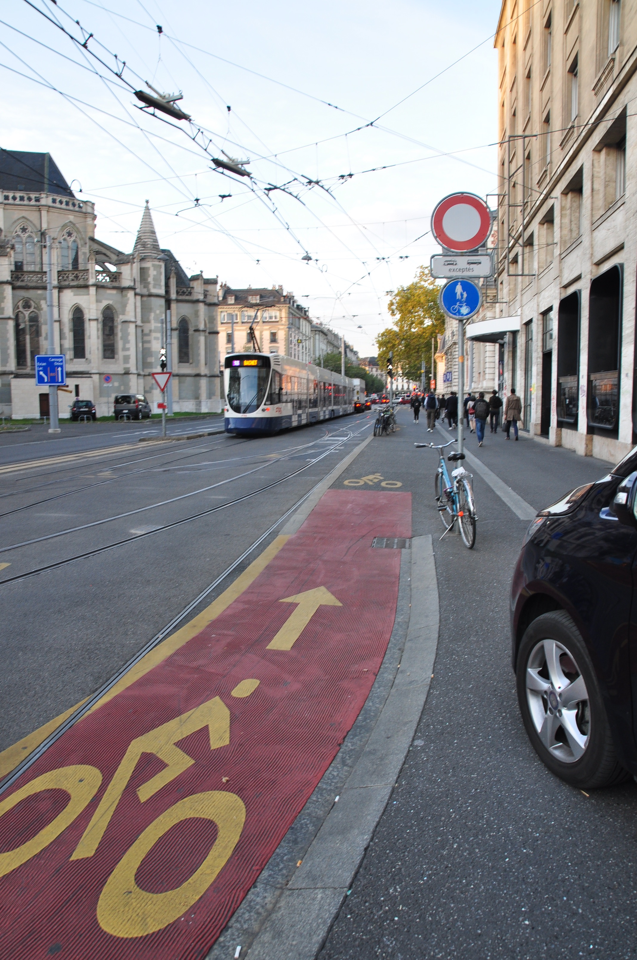 A bicycle lane merging with the sidewalk in Geneva. On the left side, the public transportation passes by, while on the right, pedestrians roam through the bicycle lane.