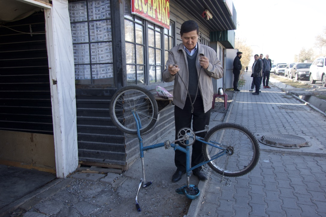 A local resident repairs repairs a bike outside of his shop.