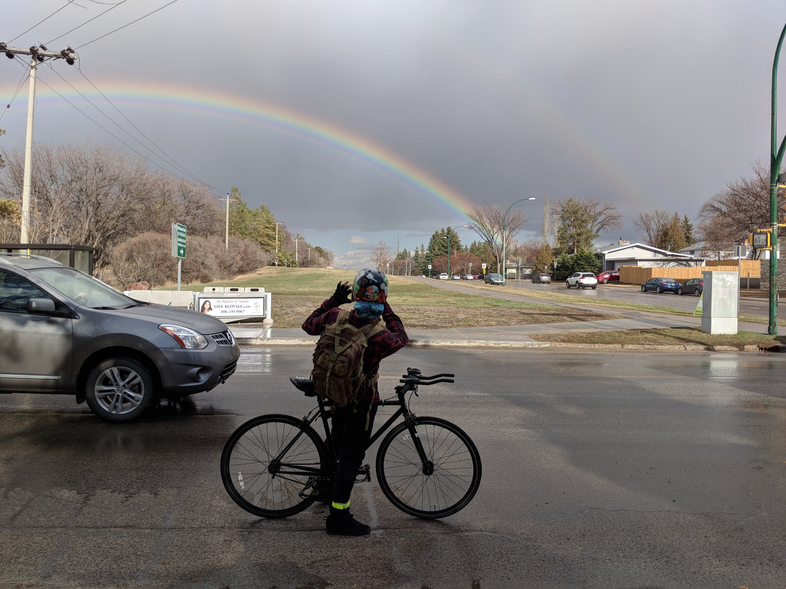 Riding a bicycle gives the freedom to stop to take a picture of an unexpected rainbow.