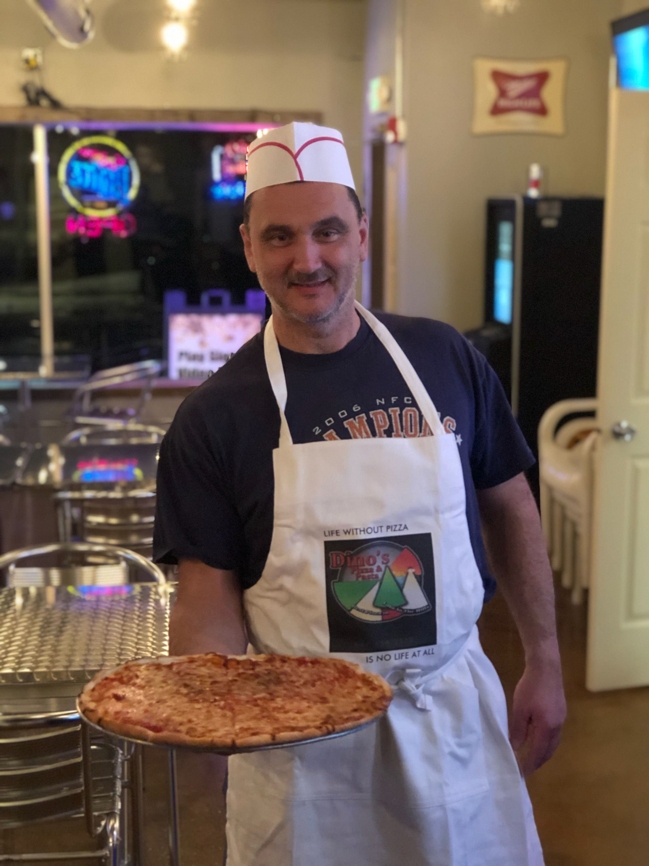 Dino proudly serving one of his delicious homemade pizzas in his new seating area.