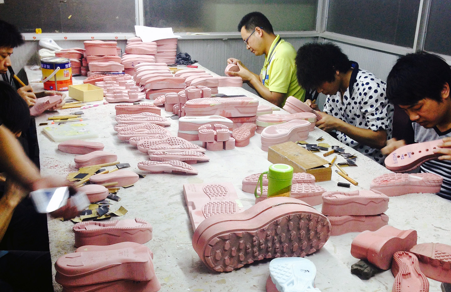 """The """"red wood"""" mock up of a sole design is being hand finished by well trained """"artists""""."""