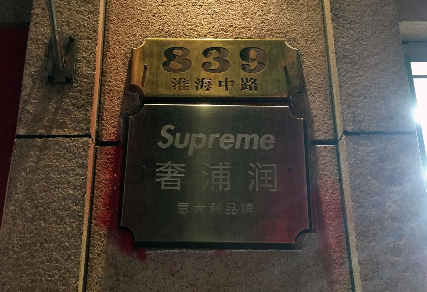 A bronze plate of SUPREME brand along with its Chinese name. Last line states it is an Italian brand.