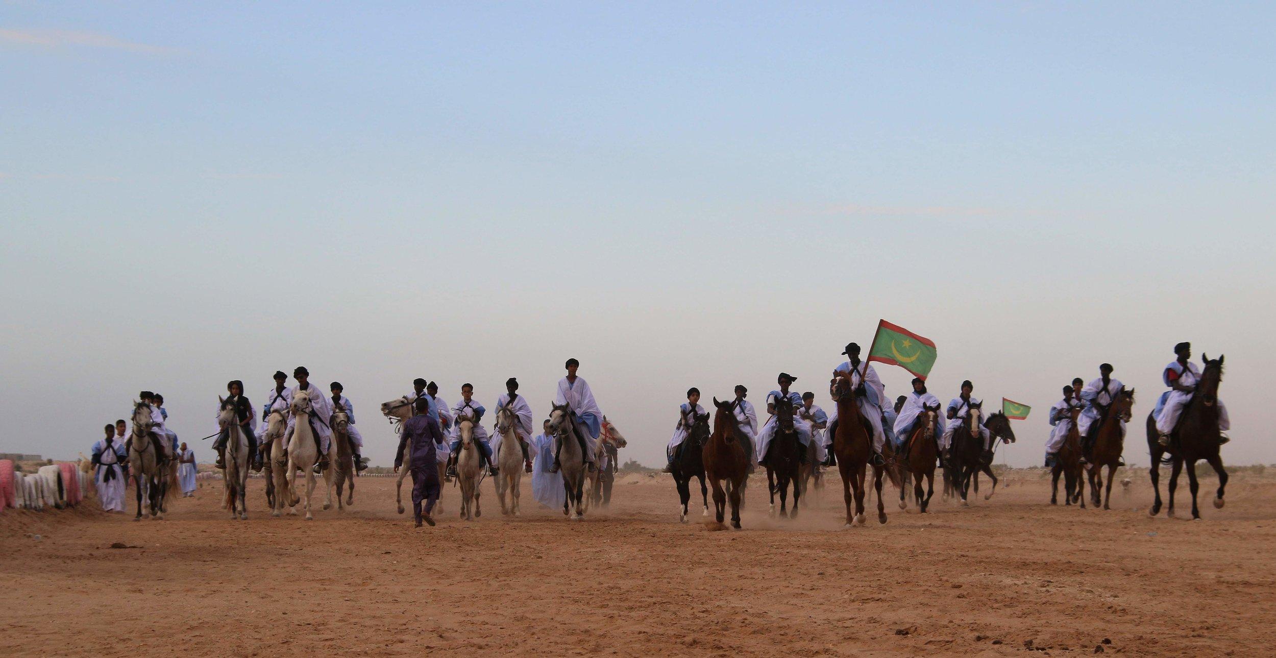 2019, Mauritanie - Dix jours de caravane culturelle dans le désert, une parade grandiose de dromadaires et de chevaux, des artistes Autochtones du Canada pour la première fois en Mauritanie, des musiciens mauritaniens et canadiens qui partagent musiques et rituels... Pour le 10e Festival Nomade, la Mauritanie vit dix journées inoubliables!Entre océan et dunes de sable, des dizaines de dromadaires et chevaux paradent à l'hippodrome de Nouakchott. Un spectacle extraordinaire qui rassemble de nombreux habitants et personnalités. Le Président de la Fédération Mauritanienne du Sport Équestre, le Professeur Sid Ahmed Mogueya, rend hommage aux valeurs des nomades.Le Festival Nomade présente aussi une soirée historique! Pour la première fois, des artistes Autochtones du Canada jouent en Mauritanie. A l'Institut Français de Mauritanie, Laura Niquay partage sa vision de la nation Atikamekw dans une ambiance folk-intimiste. Martin Akwiranoron Loft, artiste Kanien'kehá:ka, expose ses œuvres entre photographie et artisanat traditionnel.Les festivaliers découvrent d'autres artistes canadiens. Révélation Radio-Canada, Nomad'Stones fait exploser sa musique métissée. Gotta Lago, coup de cœur des Francos de Montréal, fait voyager avec ses rythmes et son énergie contagieuses.Les artistes canadiens sont chaleureusement accueillis par le public et les musiciens mauritaniens. Parmi eux : la célèbre diva Noura Mint Seymali et plusieurs artistes nomades traditionnels, jeunes et anciens.Enfin, c'est le départ d'une incroyable caravane culturelle dans le désert !!! Pendant dix jours, le Festival (vraiment) Nomade parcourt 120 km jusqu'au village d'Ivijaren. Dans l'immensité de sable, les musiciens canadiens et mauritaniens partagent avec les habitants semi-nomades du désert. Les discussions et les concerts au creux des dunes resteront gravés dans les mémoires…