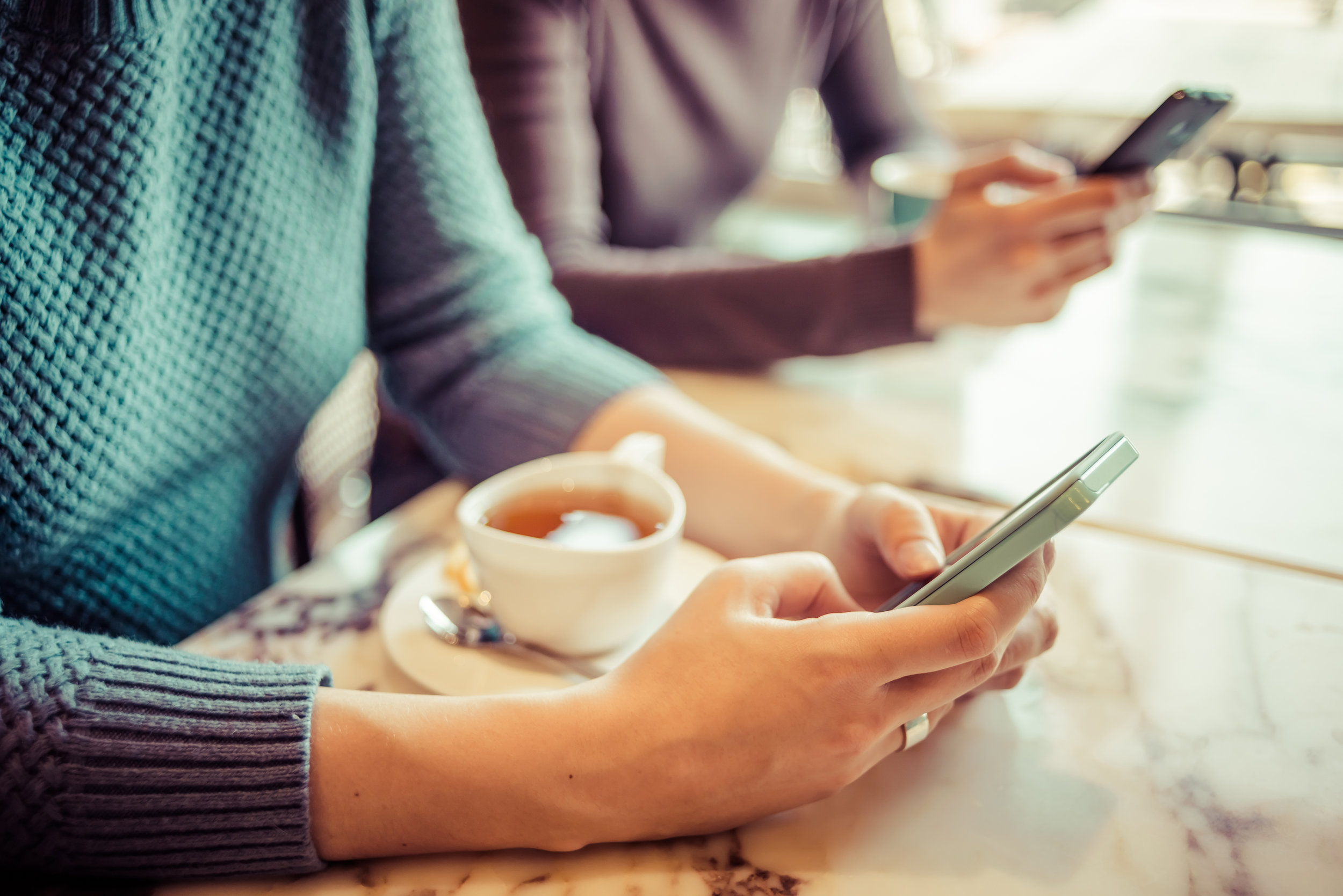 stock-photo-two-people-using-smart-phones-in-cafe-toned-picture-246252109.jpg