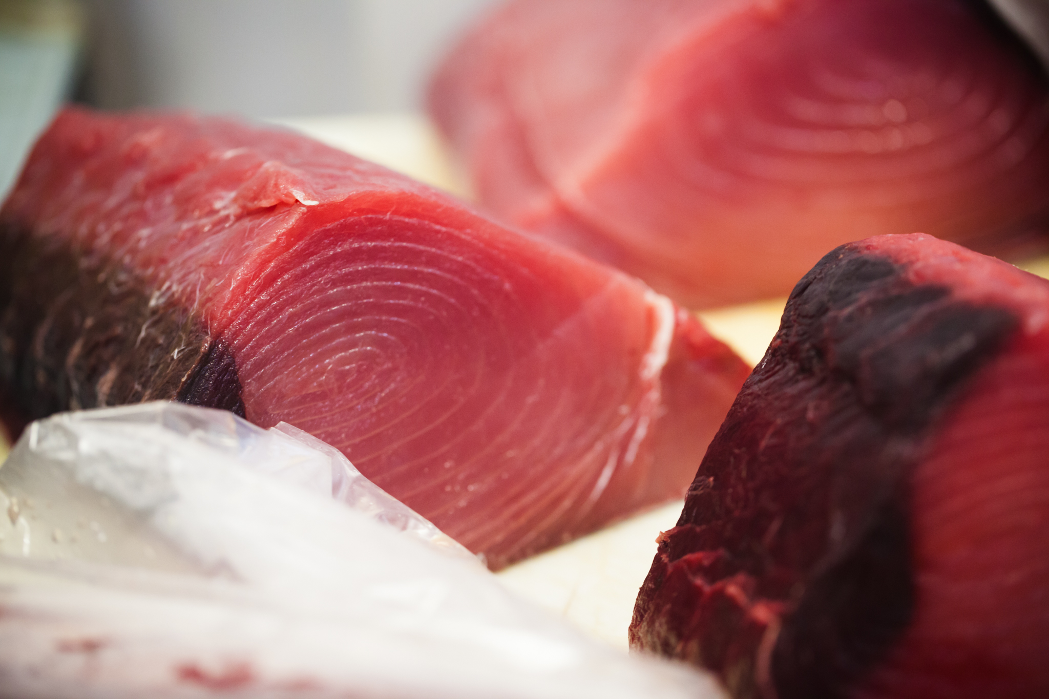 Beautiful tuna loins at our warehouse - the dark portion is the bloodline that is removed just before preparing your recipe.  The bloodline and the skin help keep the meat intact and together.