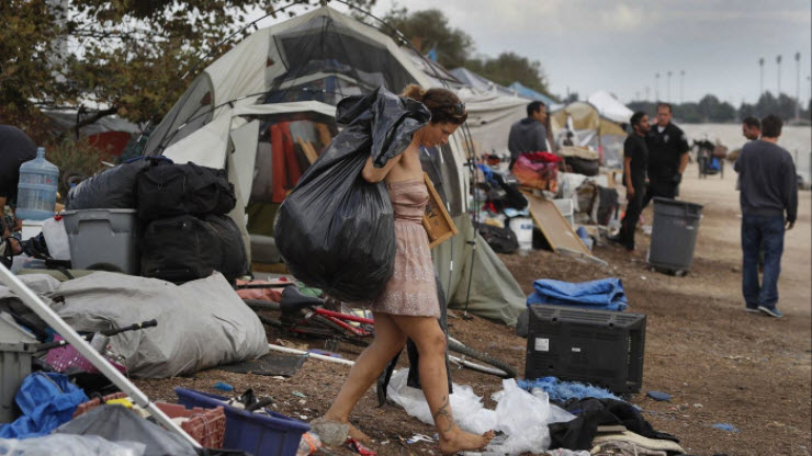 A homeless woman wearing a glamorous dress while being evicted with her belongings from a homeless encampment along the Santa Ana River on Nov. 10, 2017. (Los Angeles Times)