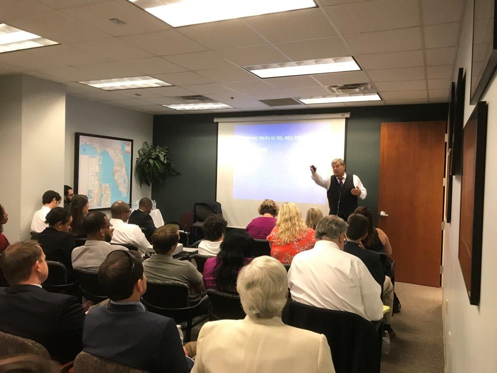 Picture of Roger J. Dodd teaching to a room full of people.