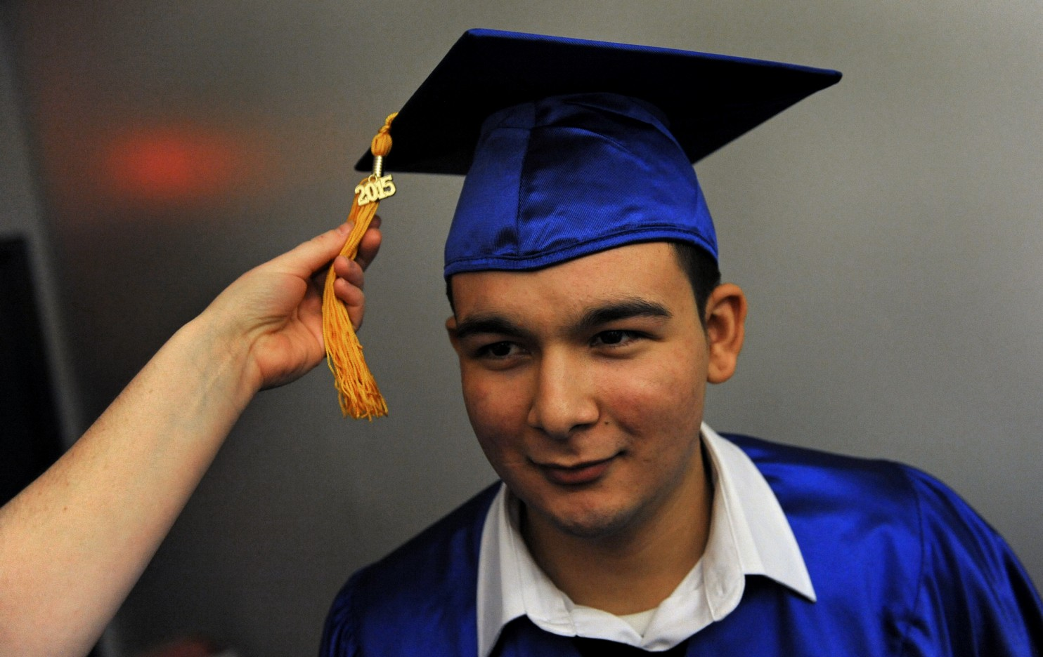 Next Step grad Guillermo Romero plans to go on to college. Adjusting his tassel is Lily Harris, a staffer at Next Step. The District is considering a proposal to give diplomas to GED recipients. (Michael S. Williamson/The Washington Post)