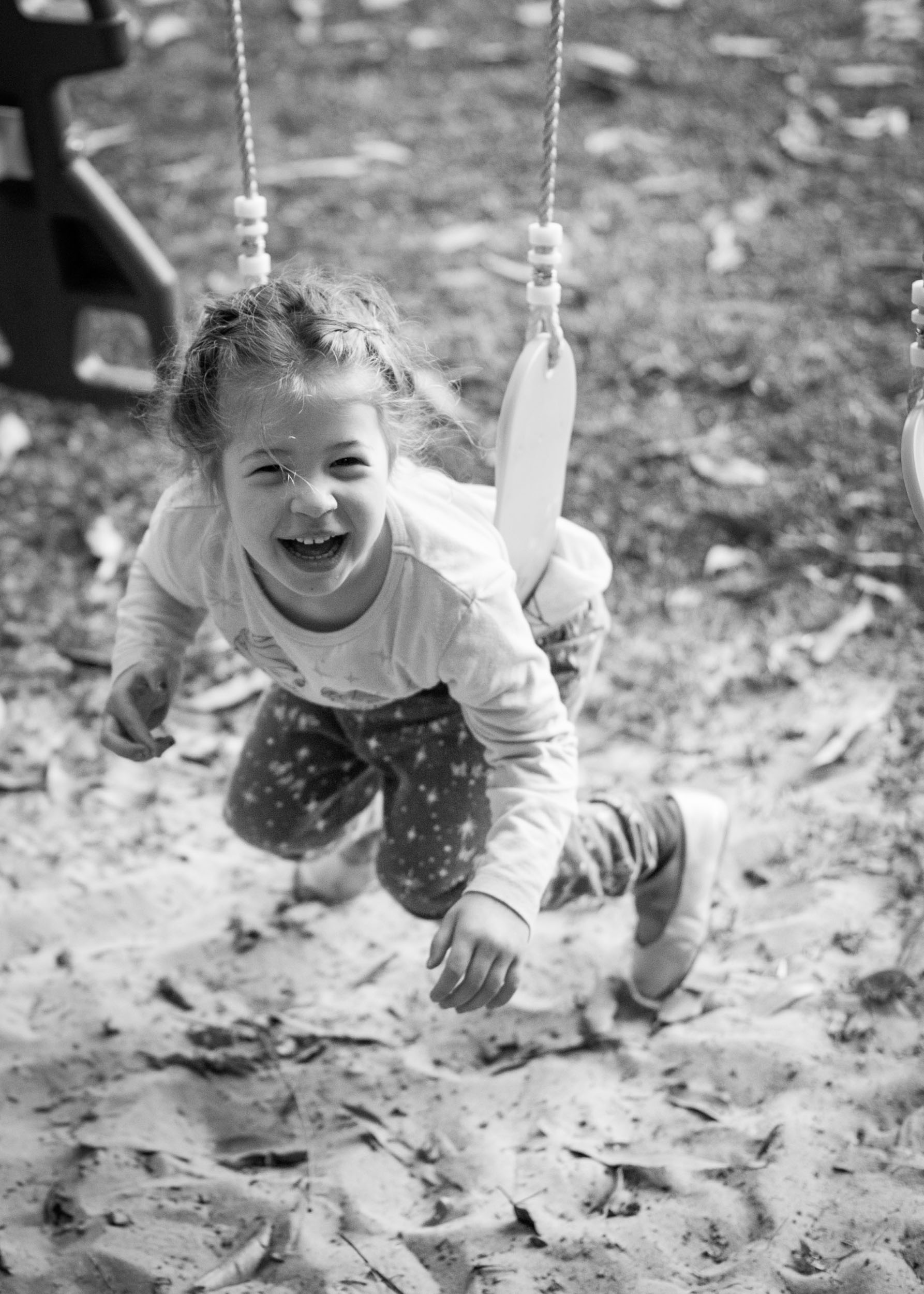little girl laughing on swing