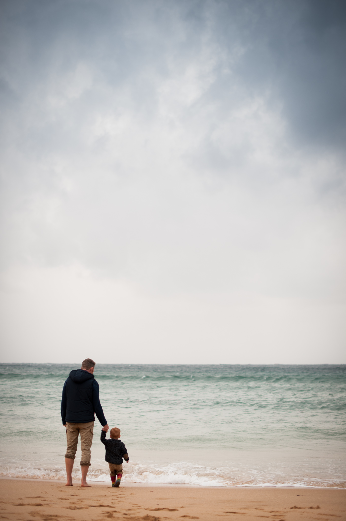 Father and son holding hands watching the waves
