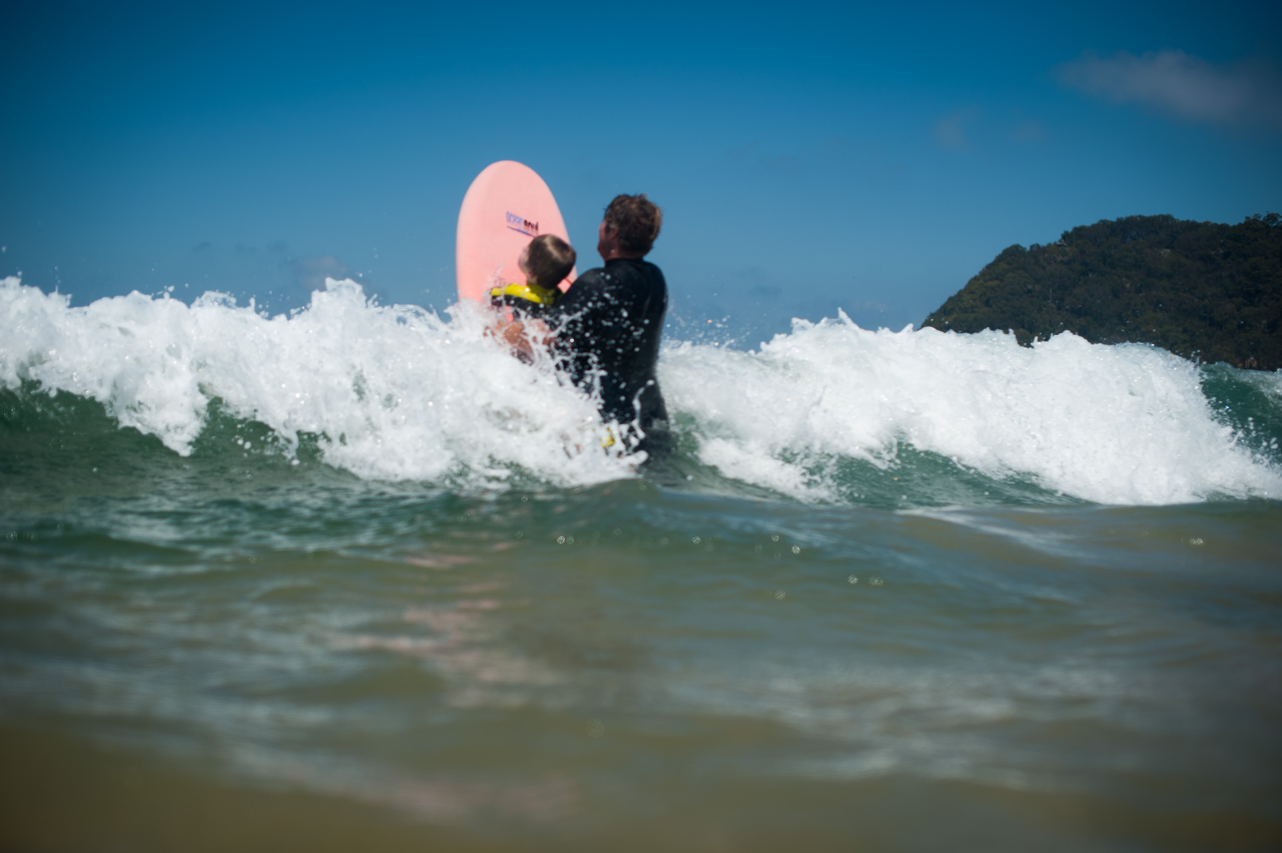 Dad pushing son over a wave at Umina Beach Central Coast NSW