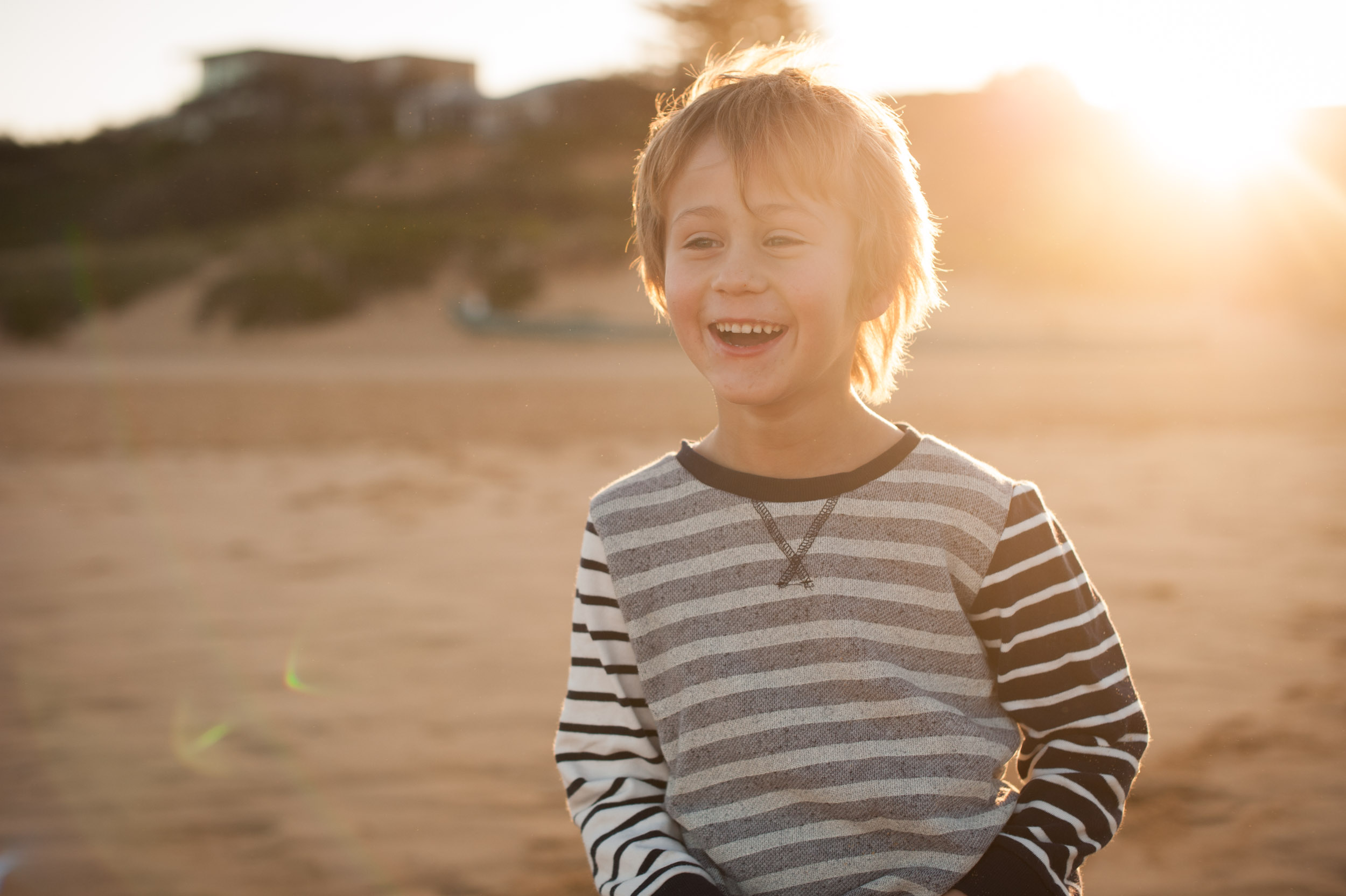 Little boy laughing at sunset at the beach