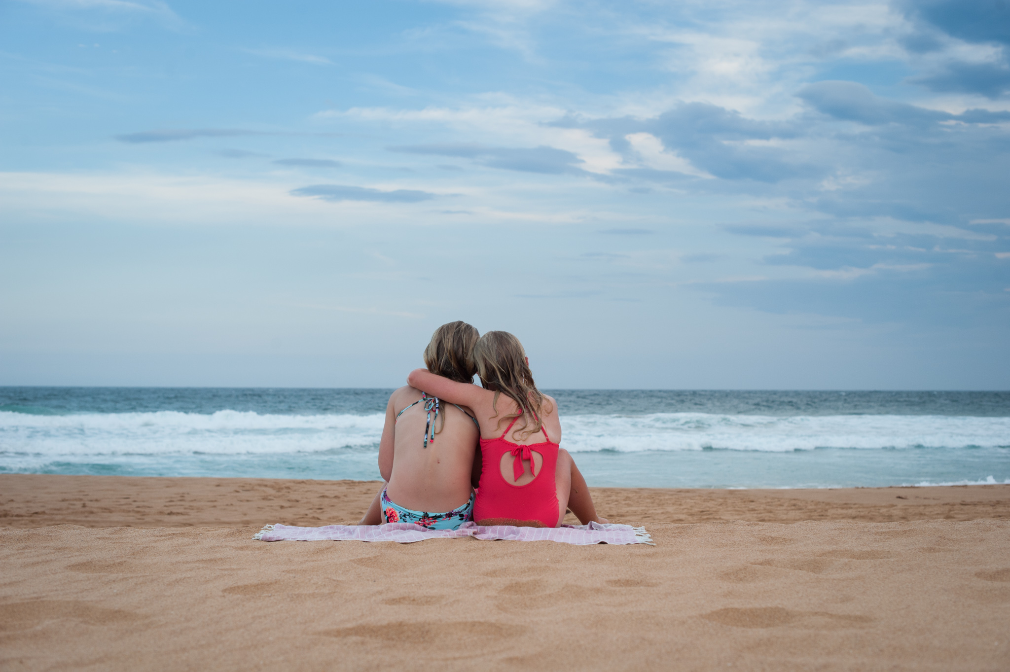 central coast family photographer sisters cuddling at the beach