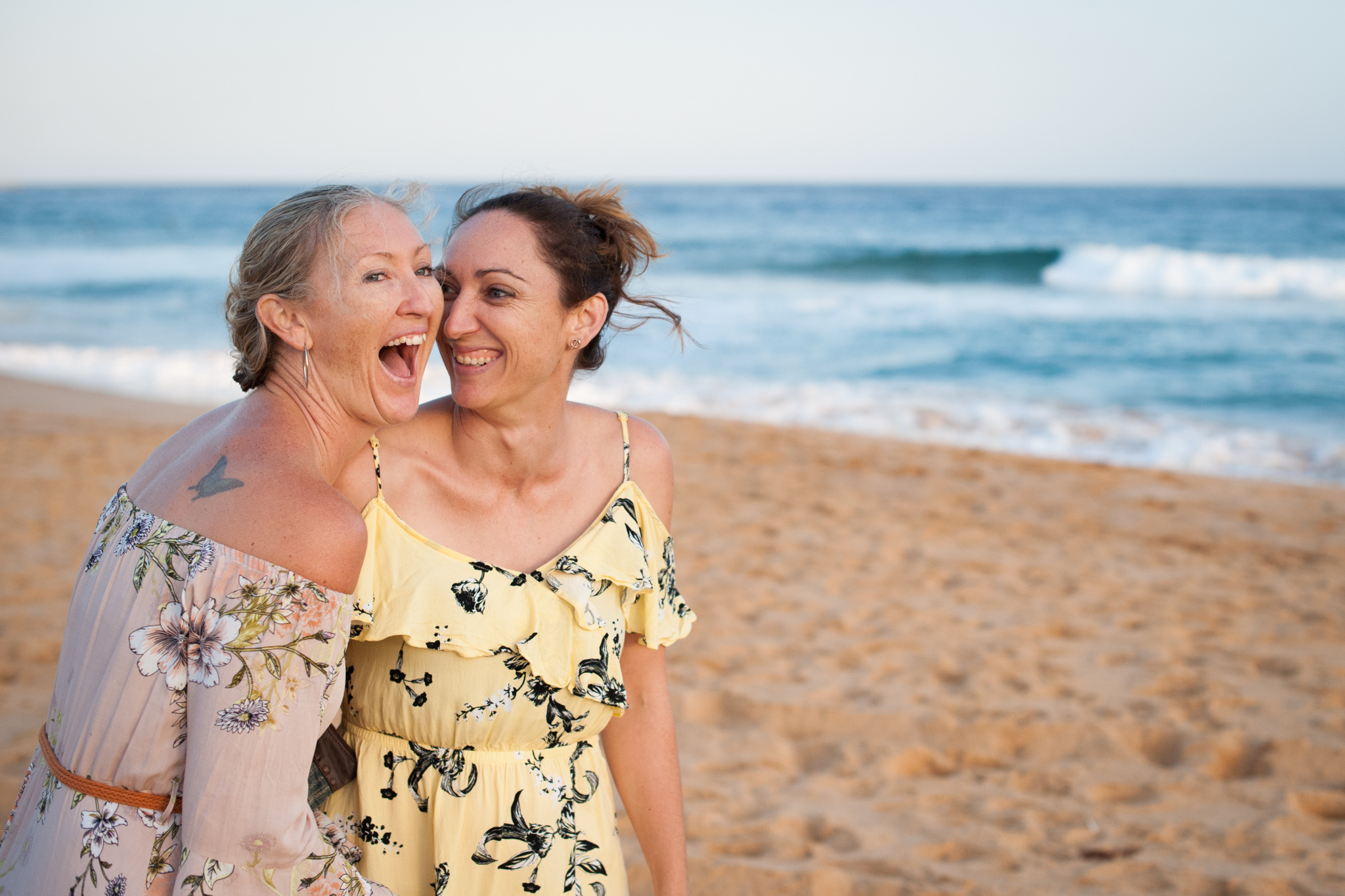 central coast family photographer sisters laughing on the beach