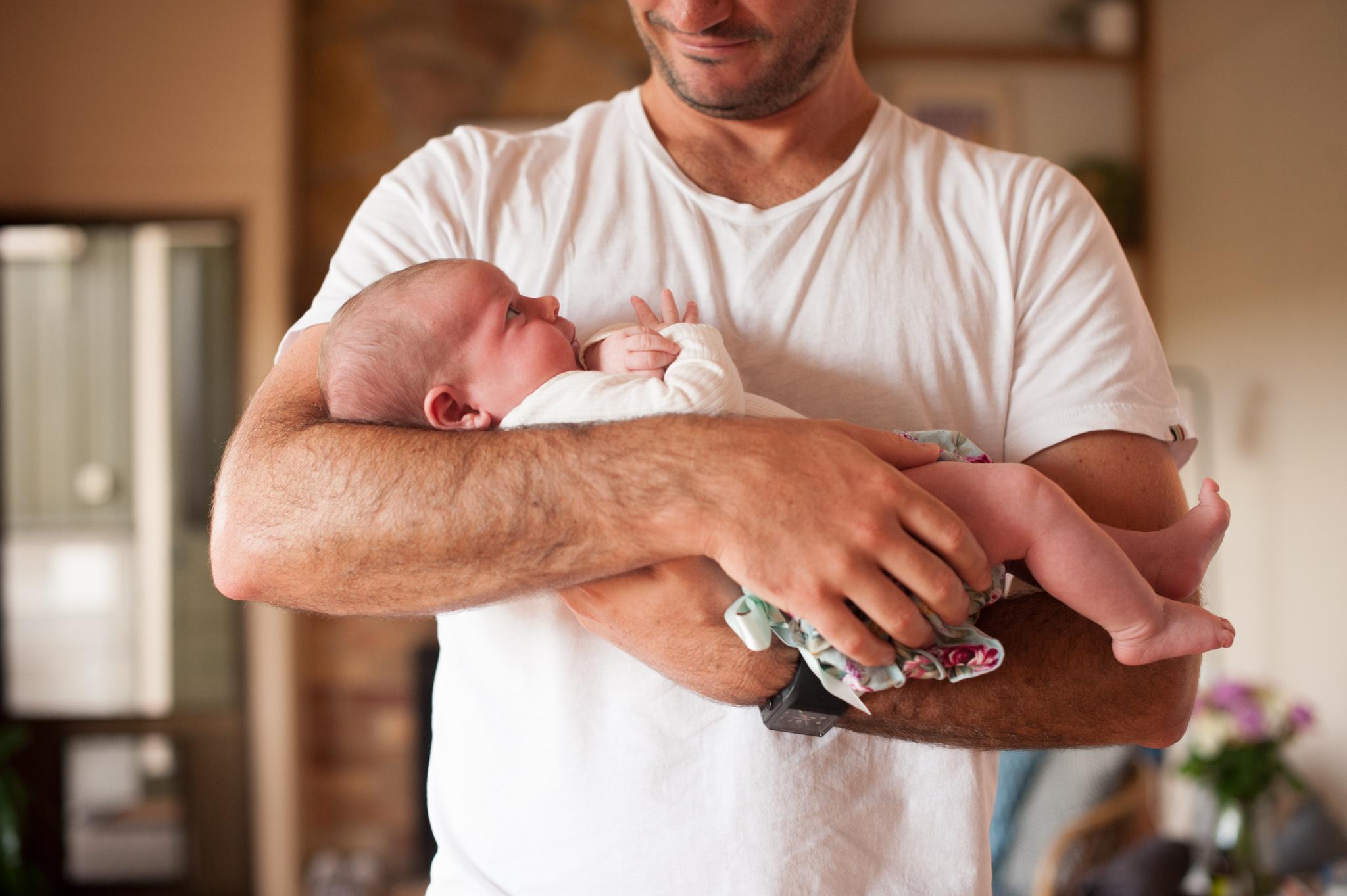 newborn baby cuddled up with daddy