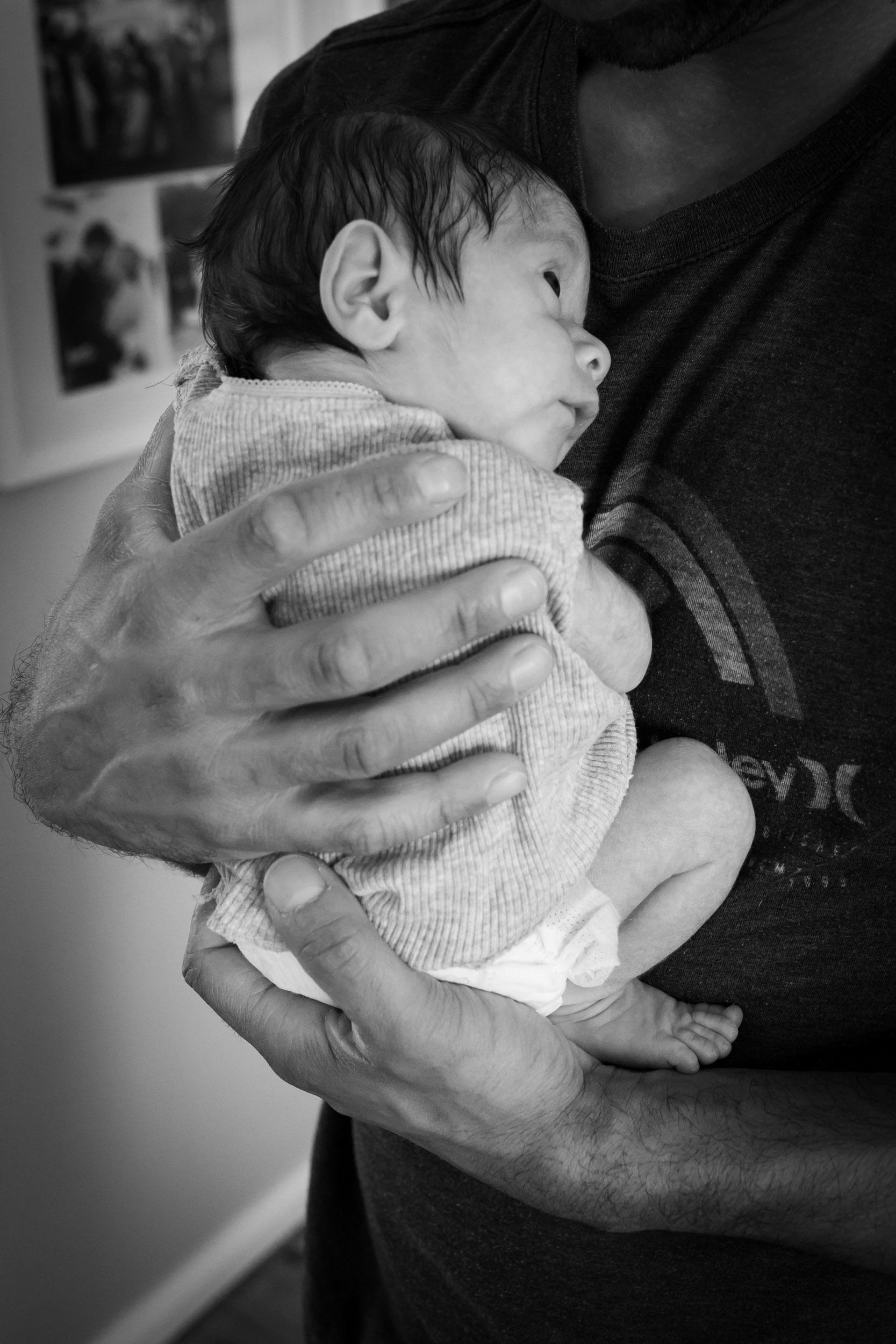 newborn baby cuddles with dad