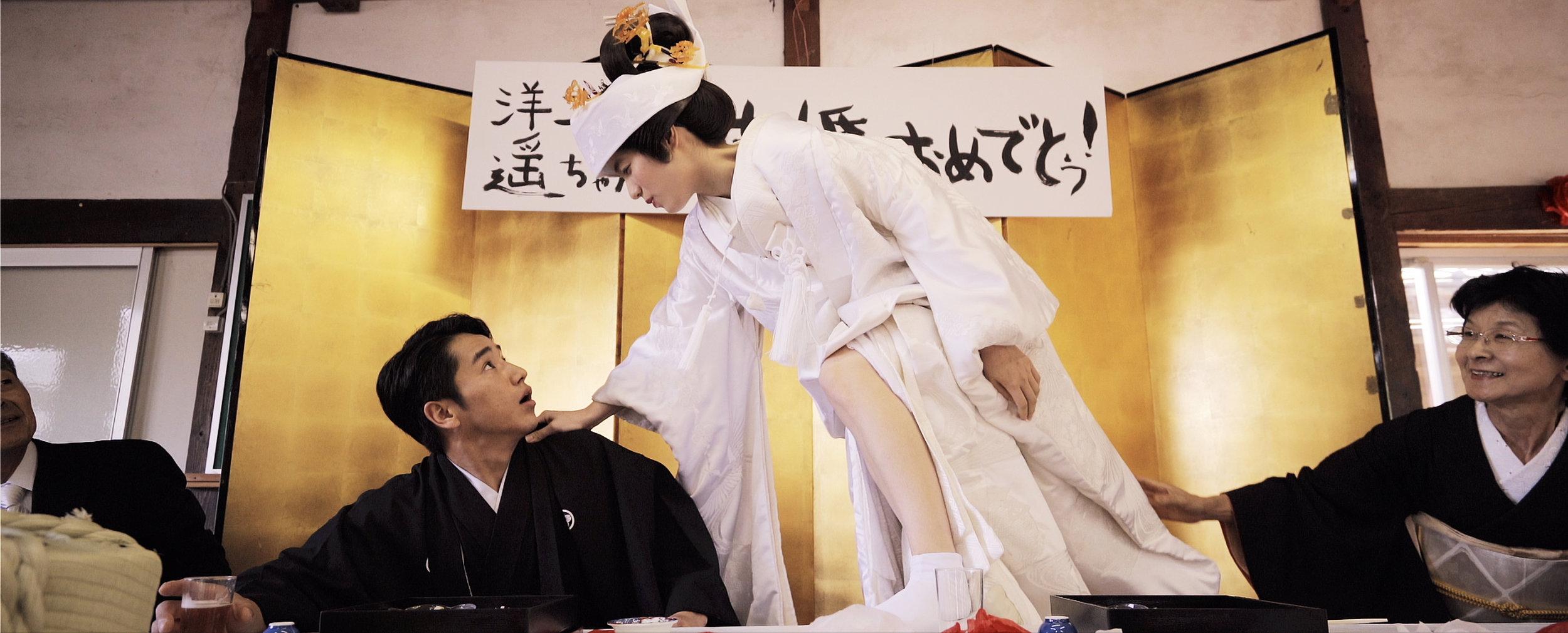 結婚式の最中 新婦の遥が泥酔し新郎に詰め寄るシーン  The drunk bride grabbing the groom's neck during the wedding