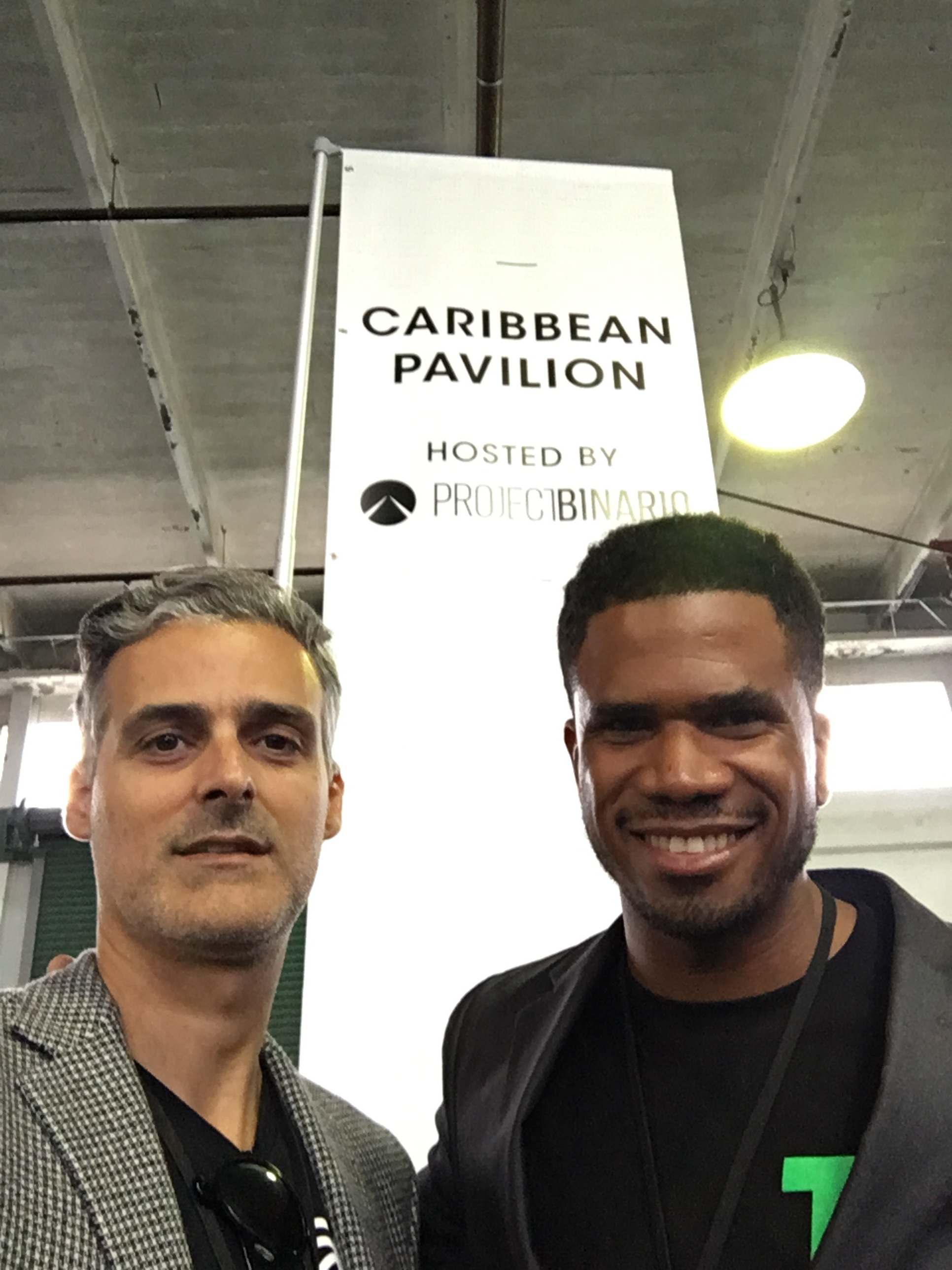 ProjectBinario's Eddy Perez and Caribbean Transit Solution's Khalil Bryan in front of the Caribbean Pavilion banner at TechCrunch Disrupt
