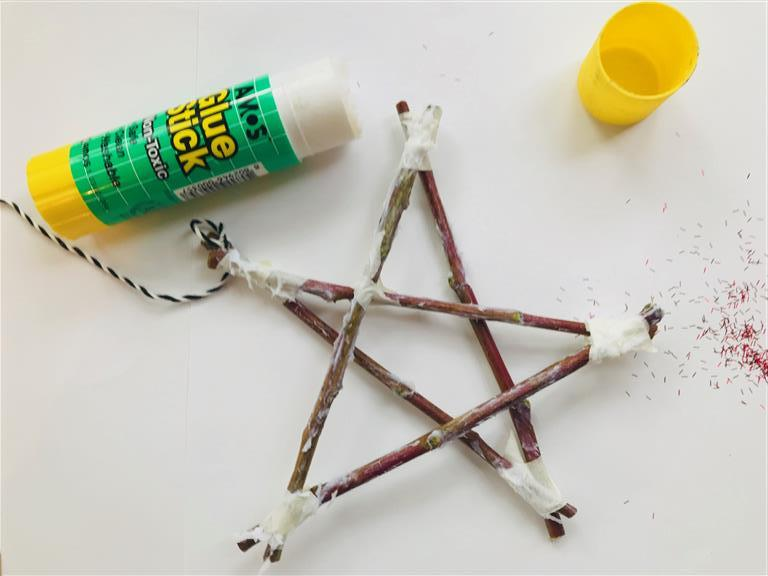 Step 8: Decorate your star. The possibilities are endless! I used glue and biodegradable glitter. First up, though, cover your sticks in glue.