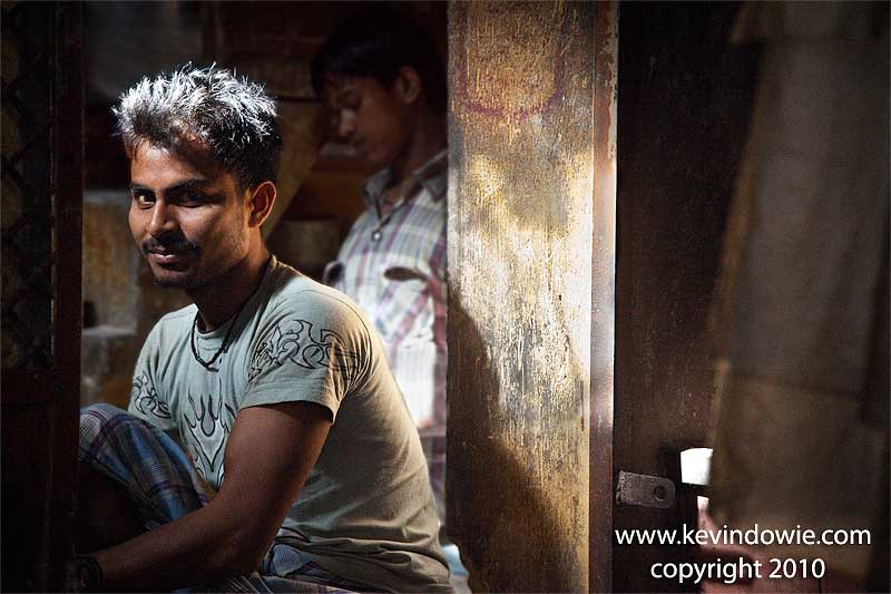 A young man pauses from his work.  Bakery, Old Delhi.