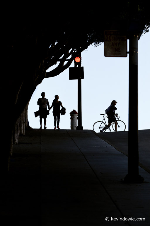 A couple, a man and a bicycle. Street scene in silhouette, San Francisco, USA.