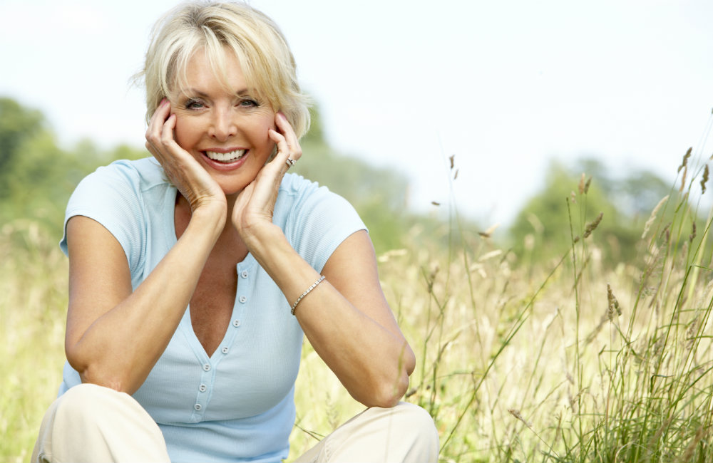 lady-sat-field-smiling-happy-tinnitus-relief