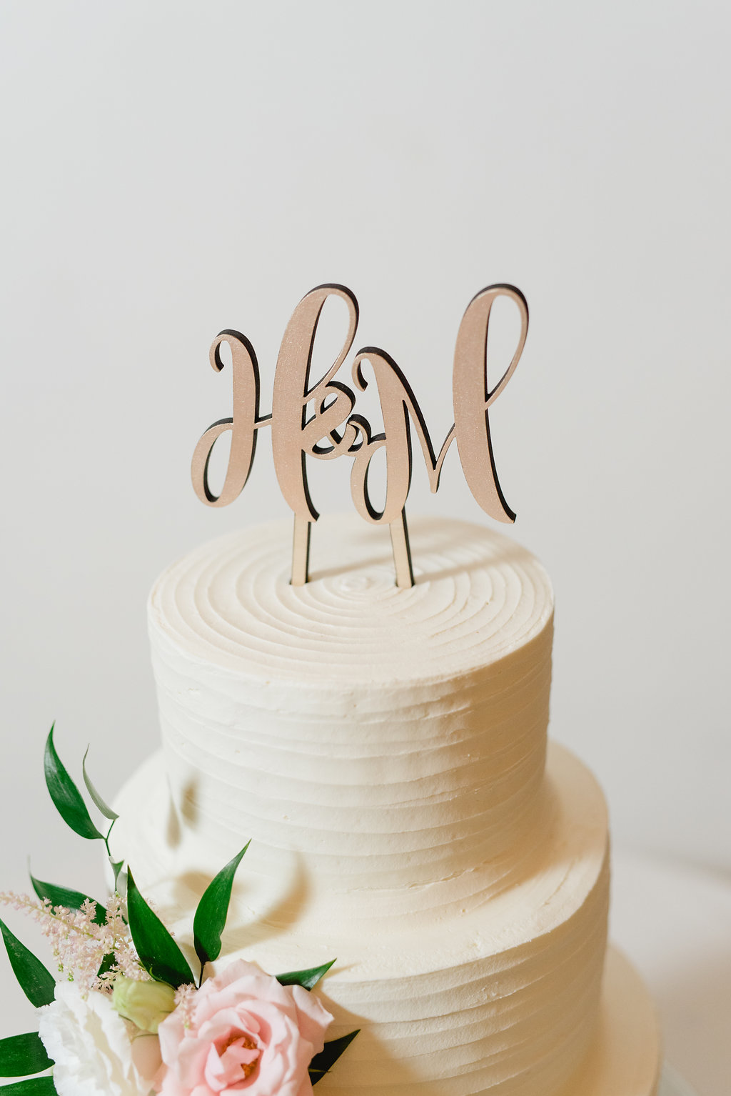 Wedding cake with flowers and initial cake topper for Pittsburgh wedding at Hotel Monaco