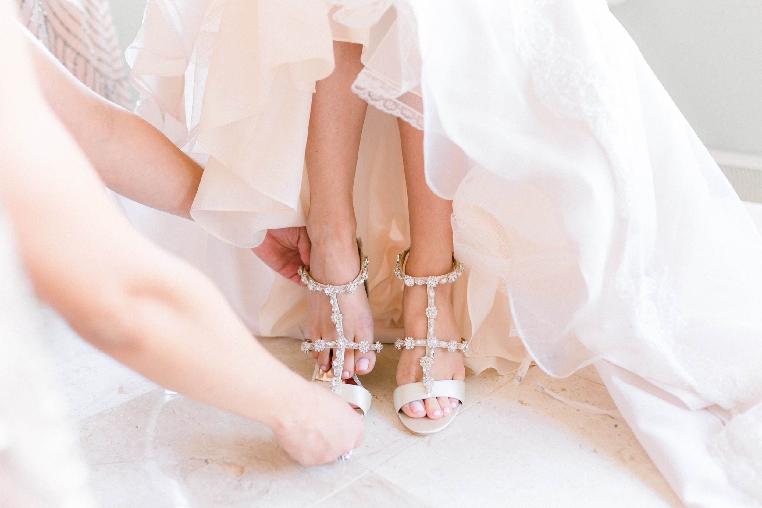 Bride putting on Badgley Mischka shoes for Pittsburgh wedding planned by Exhale Events. Find more wedding inspiration at exhale-events.com!